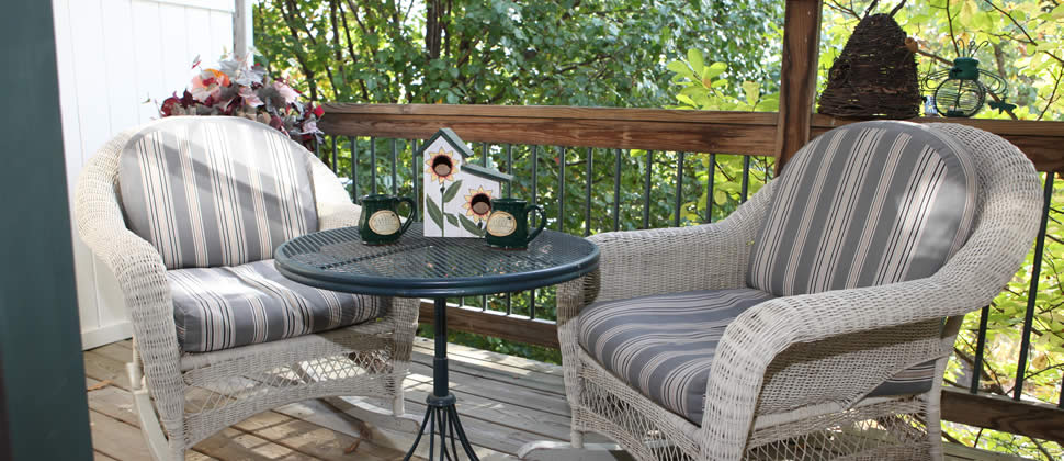 Two wicker lawn chairs and green cast iron table on wooden deck overlooking woods