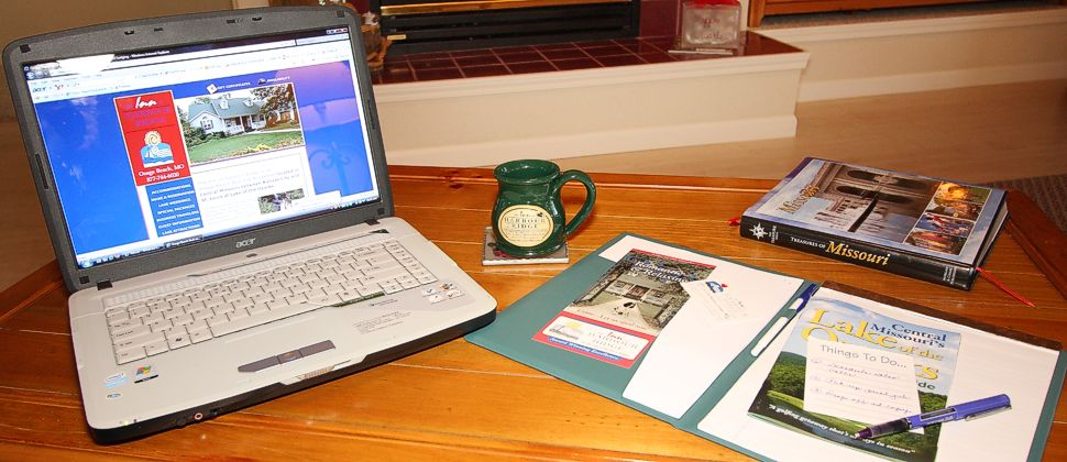 Open laptop computer on wooden desk with green mug and book and folder