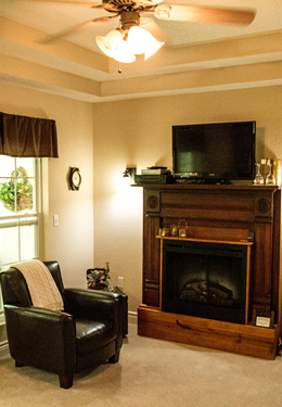 Corner of room with wood-framed fireplace, brown leather club chair and ceiling fan