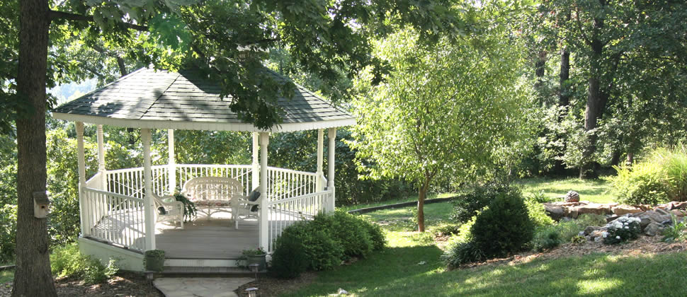 Green roofed white gazebo surrounded by green lawn with trees and bushes