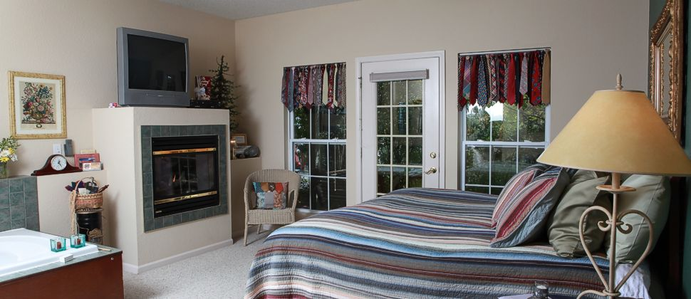 Bedroom with stucco fireplace and bed with blue and red striped bedding