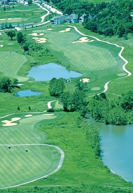 Overhead view of golf course with path winding through greens and water features