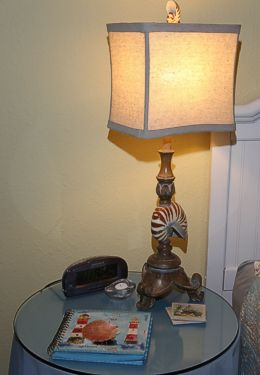 Side table with blue tablecoth, magazines and lit lamp with clock radio