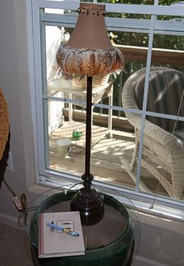 Side table made of large pot with lamp set in front of sunny window
