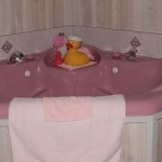 pink two-person bathtub with white paneling, rubber ducky and towels