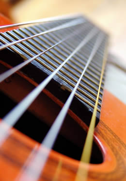 Close up of tan wooden guitar body and fret with strings