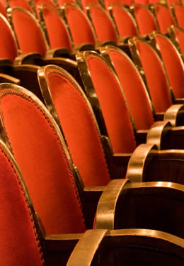 Line of red velvet chairs in theater-style seating