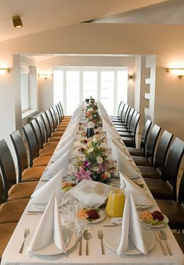 Long table set for wedding meal with flowers and white plates and linen