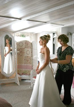 Bride dressing into white wedding gown in front of White Wicker mirror with assistance from her mother.