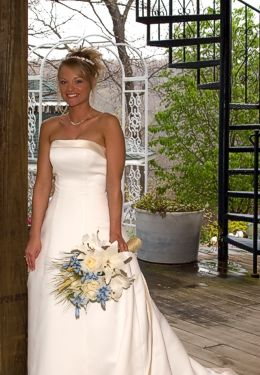 Smiling bride in white dress with cream and lavendar bouquet in front of Pergola