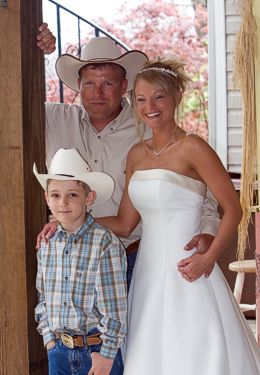 Bridal photo of Bride in a white dress, groom with cowboy hat and young boy in blue plaid shirt.