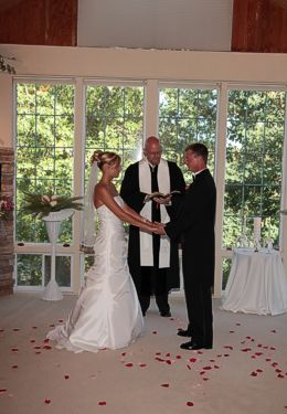Wedding ceremony showing bride and groom holding hands in front of officiant with red rose petals scattered on floor.
