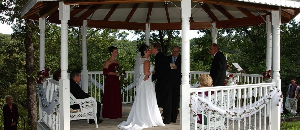 Bride and Groom kissing in white gazebo with wedding party looking on